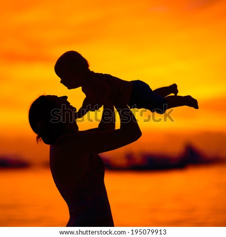 Silhouette of mother and baby at sunset - stock photo