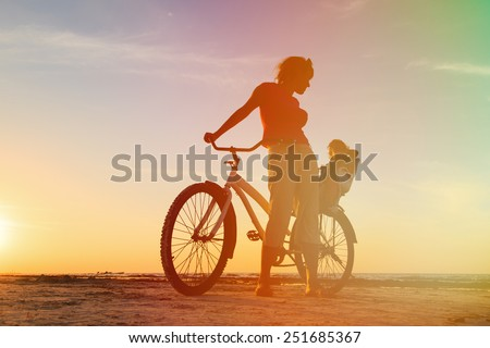 Silhouette of mother and baby biking at sunset - stock photo