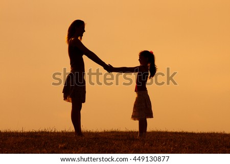 Silhouette of mother and daughter holding hands in the nature.Precious family moments - stock photo