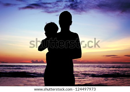 Silhouette of mother and her baby on sunset - stock photo
