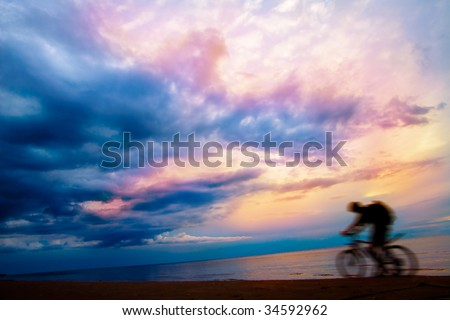 Silhouette of mountain biker on beach and sunset, stormy sky - stock photo