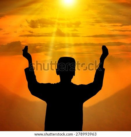 Silhouette of muslim people praying conceptual image - stock photo