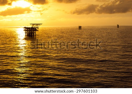 Silhouette of offshore drilling rigs at a gold colored sunset - stock photo