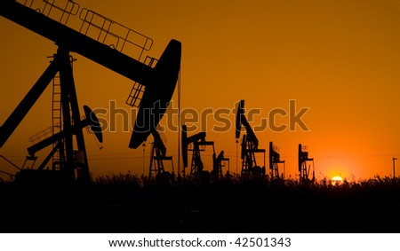 Silhouette of oil field with sunset - stock photo