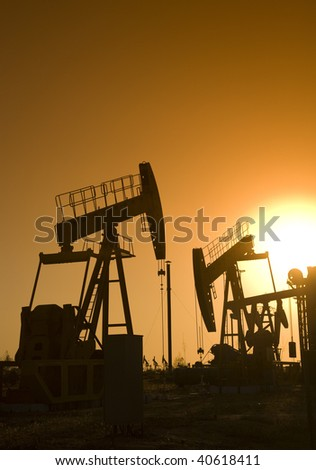 Silhouette of oil pump jack with sunset - stock photo