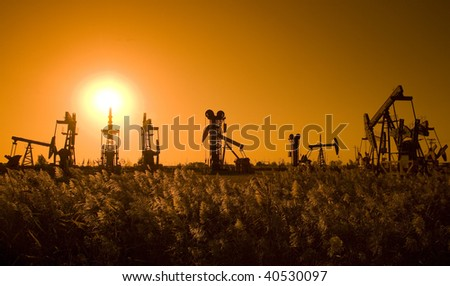 Silhouette of oil pump with sunset on the prairie - stock photo