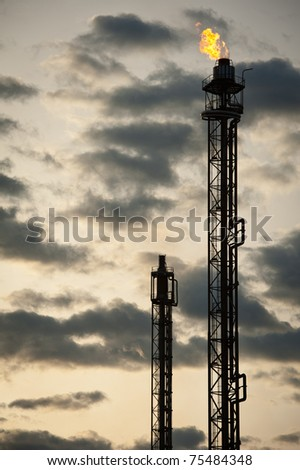 silhouette of oil refinery tower at sunset - stock photo