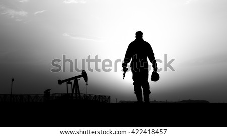 Silhouette of oilfield worker and crude oil pump in background- oilfield  - sunset - Black and white - stock photo