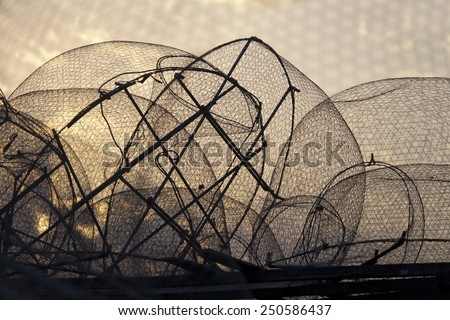 Silhouette of old fishing nets against sunrise sky - stock photo