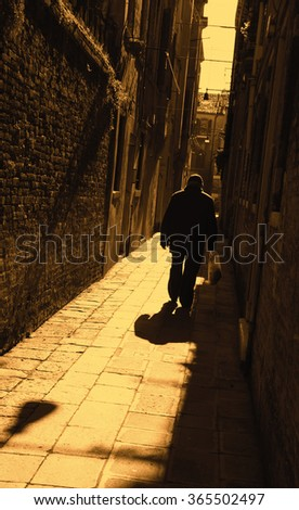 Silhouette of  old man going on narrow street in shining sun rays. (Venice, Italy) A game of light and shadow. Light spots. Sepia toned dark photo. - stock photo