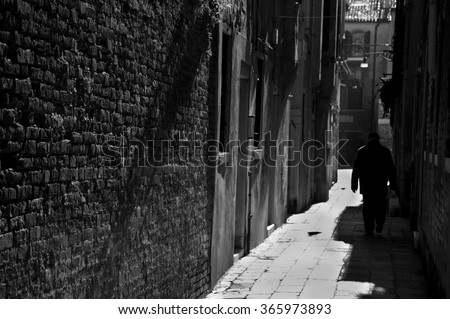 Silhouette of  old man going on narrow street in shining sun rays. (Venice, Italy) A game of light and shadow. Light spots. Dark aged photo. Black and white. Selective focus on the wall. - stock photo