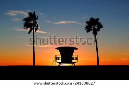 Silhouette of palm trees and classic California life guard station. Sun is setting as day turns into dusk/night and orange, red, yellow colors  fill the sky - stock photo