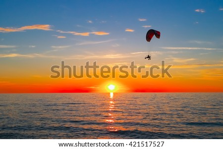 Silhouette of paraglider flying over sea at sunset - stock photo