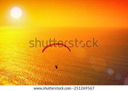 Silhouette of paraglider soaring over sea at sunset - stock photo