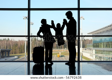 silhouette of parents holding their child for hands standing near window in airport - stock photo