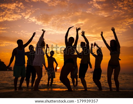 Silhouette of People Dancing On Beach at Sunset - stock photo