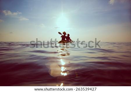 silhouette of people kayaking at sunset - stock photo