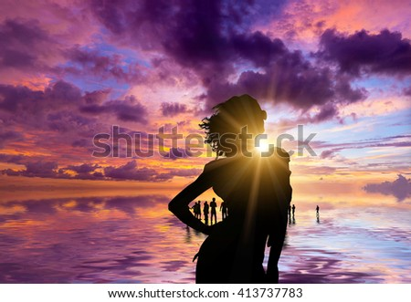 Silhouette of people on the beach at sunset - stock photo