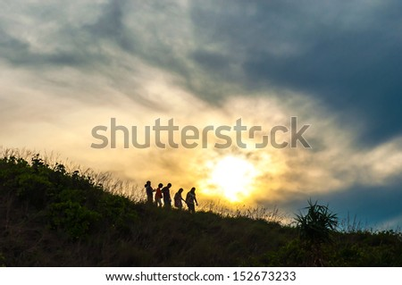 Silhouette of people walking on the mountain against vivid sunset sky,thailand - stock photo