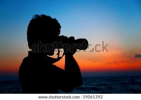 Silhouette of photographer ashore on sunset - stock photo