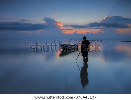 Silhouette of photographer looking to the boat near the beach when during sunrise. Nature Photography  - stock photo