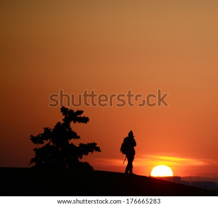 Silhouette of photographer with his equipment during sunset - stock photo
