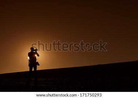 Silhouette of photographers in desert Sahara on sunset, Morocco - stock photo