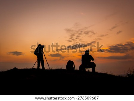 Silhouette of photographers with beautiful sky - stock photo