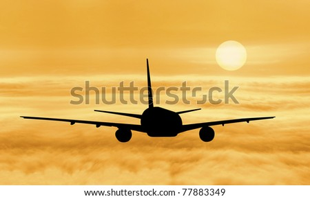silhouette of plane fly over cloud during sunrise - stock photo