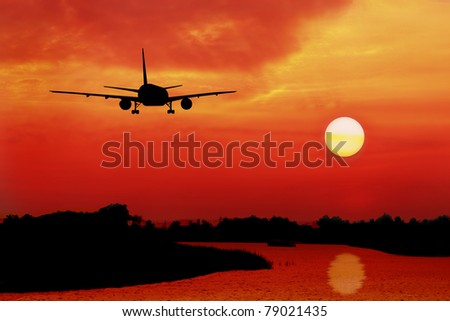 silhouette of plane fly over land and river during sunrise - stock photo