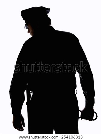 Silhouette of police officer with handcuffs in hand - stock photo