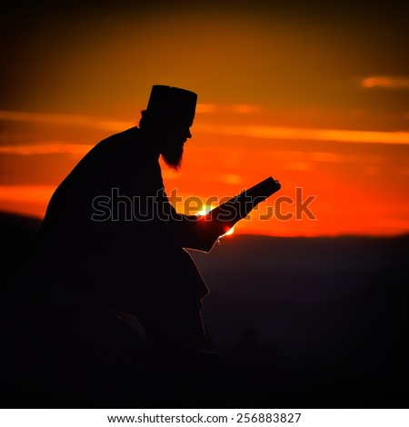 silhouette of priest reading in the sunset light, Romania, Ceahlau - stock photo