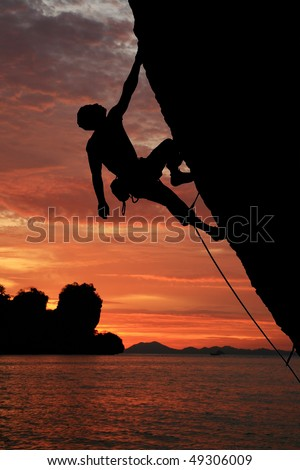 silhouette of rock climber climbing an overhanging cliff with sunset over the ocean background - stock photo
