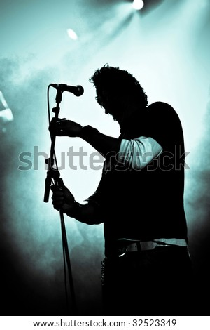 silhouette of rock singer live on stage - stock photo