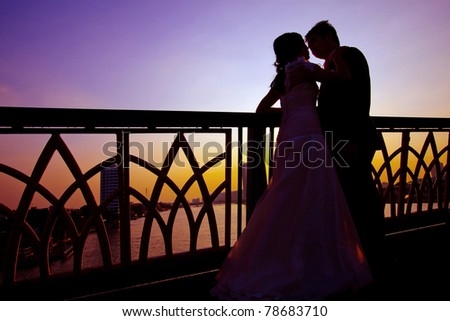 silhouette of romantic and happiness couples on the bridge over the river - stock photo