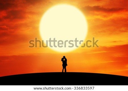 Silhouette of romantic couple standing on the hill and kissing at sunset time - stock photo