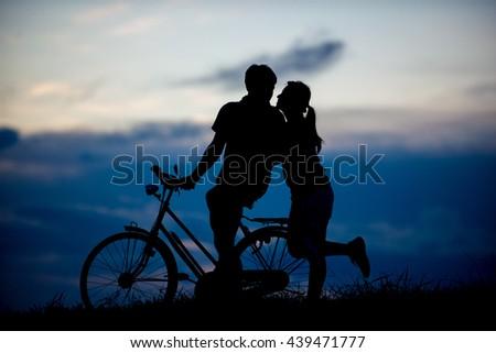 Silhouette of romantic love. sunset - stock photo