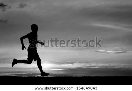 Silhouette of running man on sunset fiery background. Black and white. Element of design. - stock photo