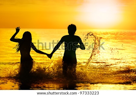 Silhouette of sea bathing of young couple against sunset. - stock photo
