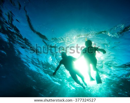 Silhouette of senior couple swimming together in tropical sea - Snorkeling tour in exotic scenarios - Concept of active elderly and fun around the world - Soft focus due to backlight and water density - stock photo