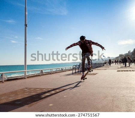 Silhouette of Skateboarder jumping in city on background of promenade and sea - stock photo