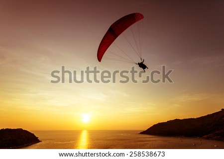Silhouette of sky diver flies on background of sunset sky and sea - stock photo