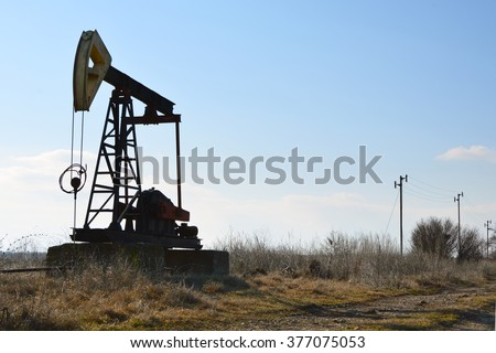 Silhouette of small Pump Jack - stock photo