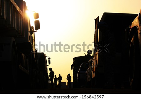 Silhouette of soldiers with vehicle - stock photo