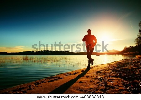 Silhouette of sport active man running and exercising on the beach at sunset.  - stock photo