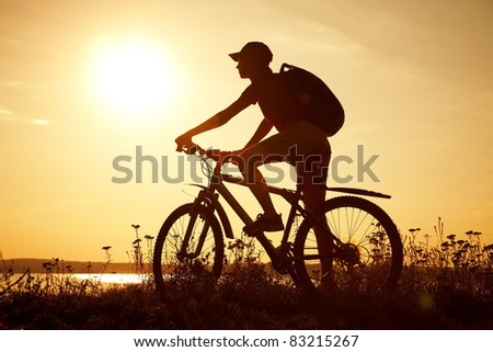 Silhouette of sports person cycling on the field on the beautiful sunset - stock photo