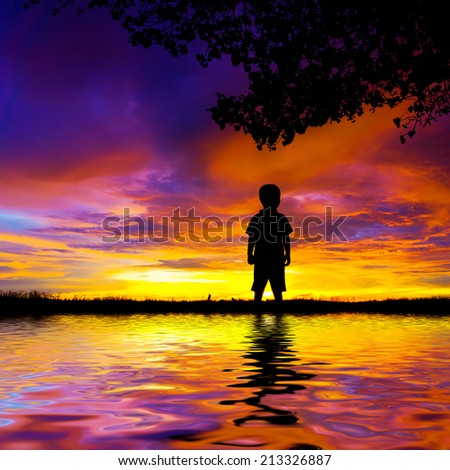 Silhouette of standing boy during sunset. digital compositing, colour tone, water reflection and ripple effects. - stock photo