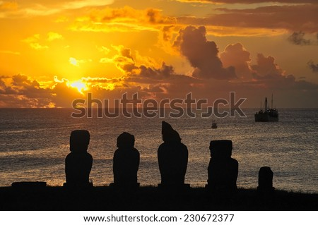 Silhouette of standing Moais at sunset in Easter Island, Chile - stock photo