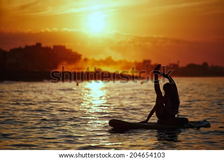 Silhouette of standup paddle boarding performed by beautiful athletic girl, orange sunset reflected in the sea, yoga at perfect sunset, spiritual meditation and relax - stock photo