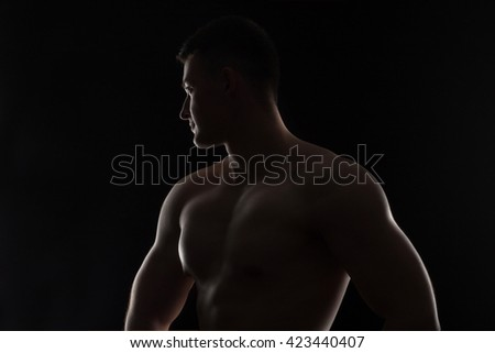 Silhouette of strong athletic man on black background - stock photo